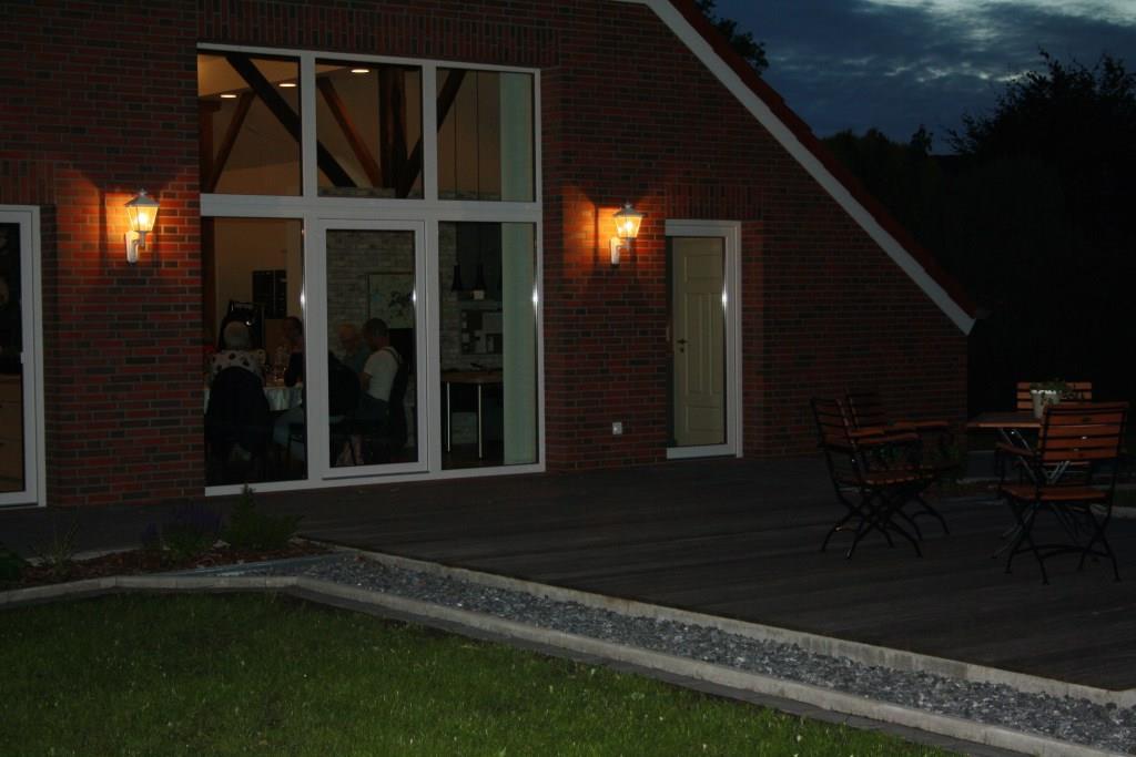 Die Gäste genießen den Blick in den abendlichen Garten